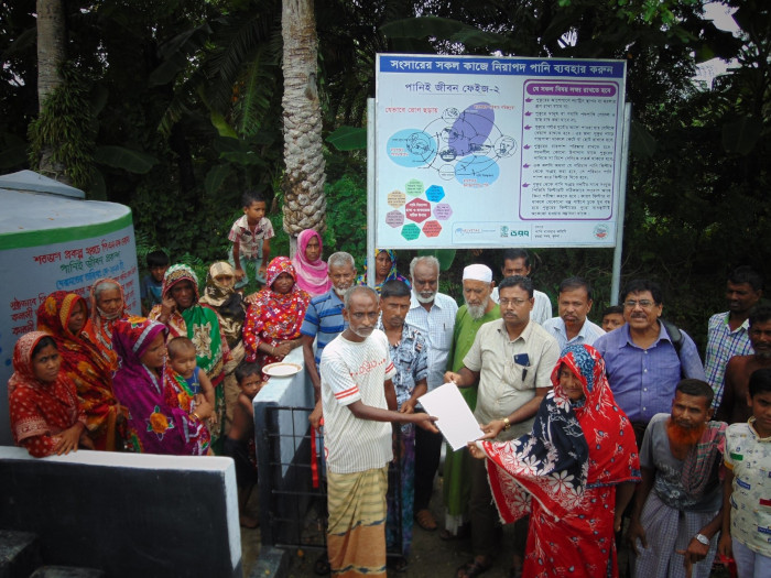 Mother's Parliament being handed over a water point by local government official